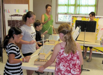 Teresa McCreary works with children learning to play the Orff instruments.