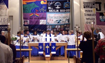 The choir concludes Advent Procession singing around the altar surrounded by AIDS quilt panels.
