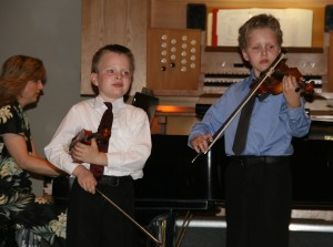 Two young violinists, accompanied by their mother