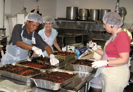 Members serve dinner to the guests at IHS, a full-service homeless shelter in Honolulu, on the third Friday of every month.